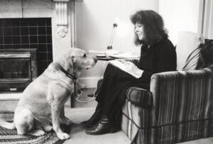 Diana Wynne Jones sitting on a chair with a dog in front of her