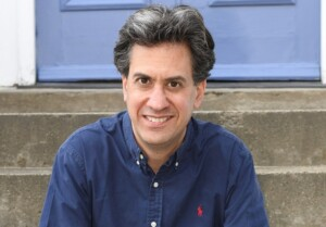 Ed Miliband sitting on steps in front of a blue door